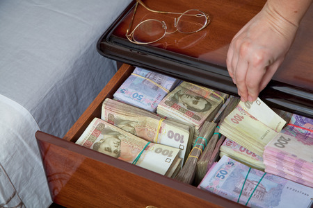 bedside table: Hand pulls out banknote and wad of money from the bedside table filled with Ukrainian cash Stock Photo