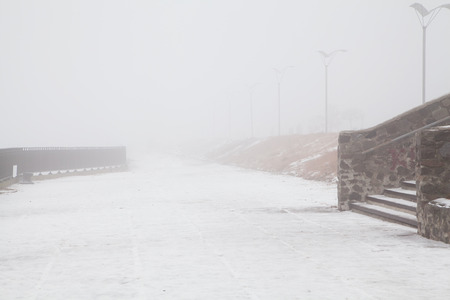 street lights: Embankment with stone fences and several street lights in the fog in winter