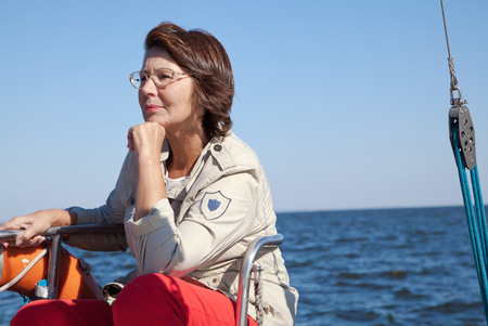 yachtsman: Elderly woman yachtsman sitting on the stern of sailing yacht at sunny day Stock Photo