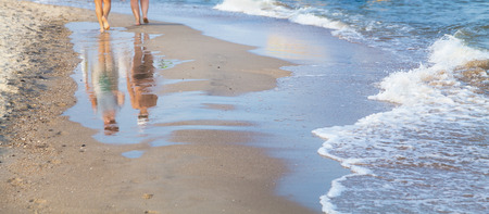 Female feet on the sea beach in wave at summer sunny day Фото со стока