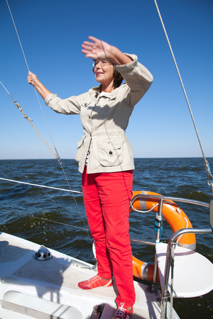 yachtsman: Elderly woman yachtsman on a sailing yacht holds on to the ropes at sunny day Stock Photo