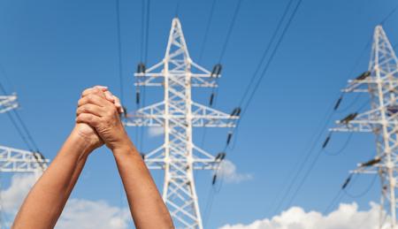 mani incrociate: Le mani incrociate in segno di assenso sullo sfondo di linee di trasmissione di potenza e il cielo blu Archivio Fotografico