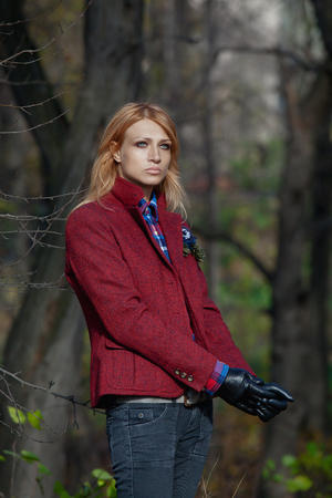 tweed: Pretty woman with flowing hair in tweed jacket and leather gloves walking in autumn forest Stock Photo