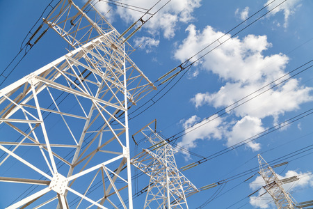 Power transmission high voltage lines on the white supports against blue sky