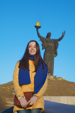 national colors: Young girl dressed in Ukrainian national colors standing on the background of monument to liberators and smiling happily at autumn sunny day Stock Photo