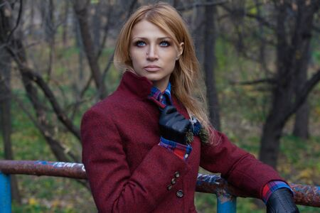 short gloves: Beautiful blonde woman in jacket and leather gloves leaning against handrail