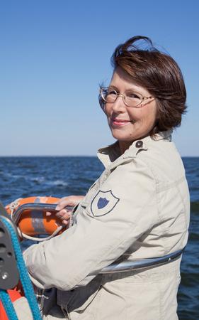 yachtsman: Elderly woman yachtsman on a sailing yacht at sunny day Stock Photo