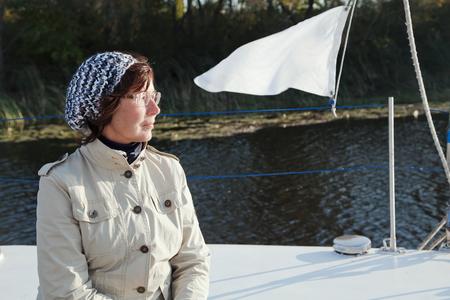 yachtsman: Elderly woman yachtsman looks afar on a sailing yacht at sunny day