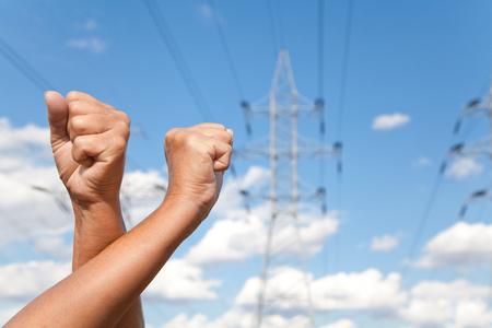 mani incrociate: Mani incrociate mostra i pugni sullo sfondo di linee di trasmissione di potenza e il cielo blu Archivio Fotografico