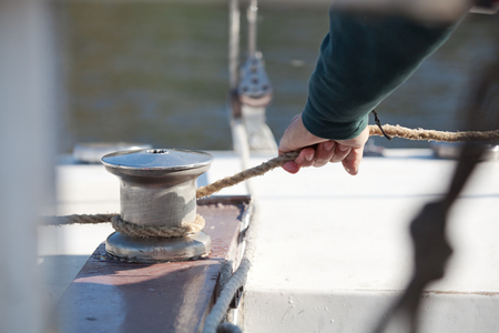 winch: Strong mans hand pulls the rope around winch of sailboat closeup Stock Photo