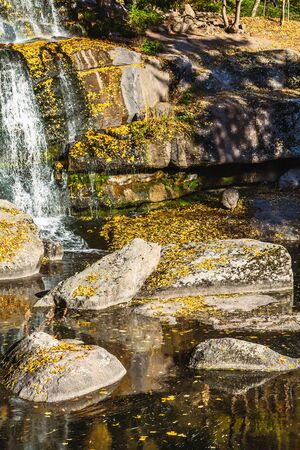 large rocks: Beautiful waterfall between large rocks in the autumn forest. sofievskiy park in Uman, Ukraine