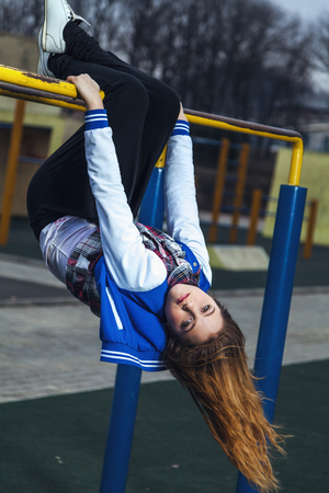 metal bars: Cute girl with long hair hanging upside down on the metal bars of the town sports