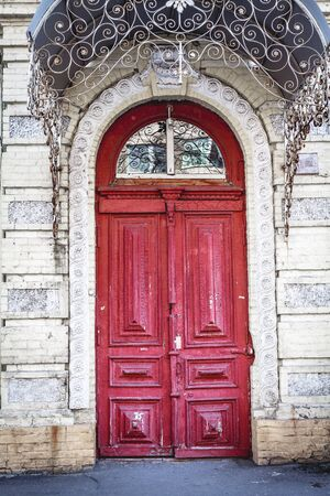 transom: Red wooden door in an old building with arched entrance Stock Photo