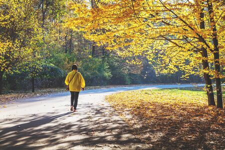 goes: woman in a yellow jacket goes on the road in the autumn forest on a sunny day Stock Photo