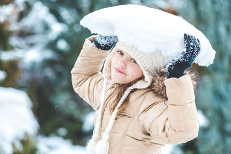 holding aloft: Young happy girl in yellow jacket holding aloft a large chunk of snow