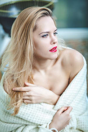 bare shoulders: Young attractive woman with bare shoulders holding a white blanket