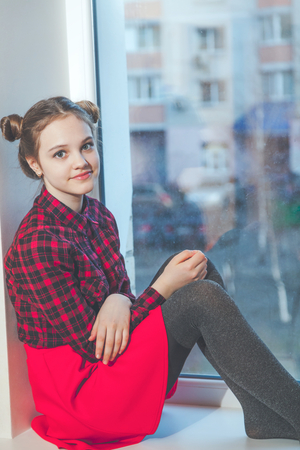 Young girl in a red skirt and a plaid shirt sitting on the windowsill Stock Photo