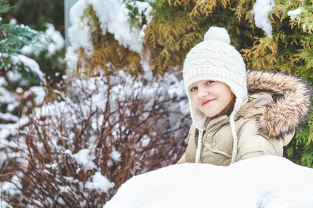knit cap: Pretty young girl in a jacket and knit cap lying in the snow against the backdrop of green pine needles