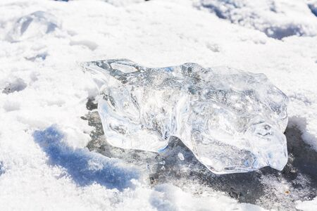 thawed: Piece of clear ice is melted in sun on the white snow