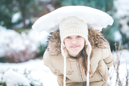 compacted: Cheerful young girl in winter clothes and leaned on his head holding a piece of compacted snow Stock Photo
