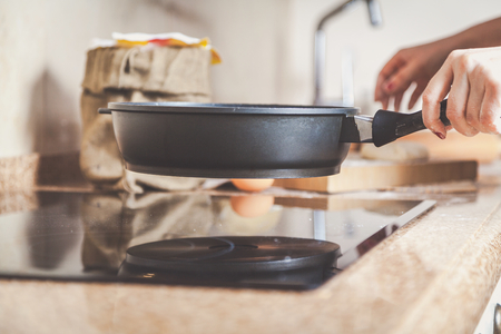 electric stove: Female hand holding a frying pan over a smooth surface electric stove