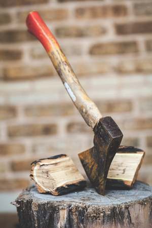 Hatchet sticking in a stump, the two halves of split logs are next Stock Photo
