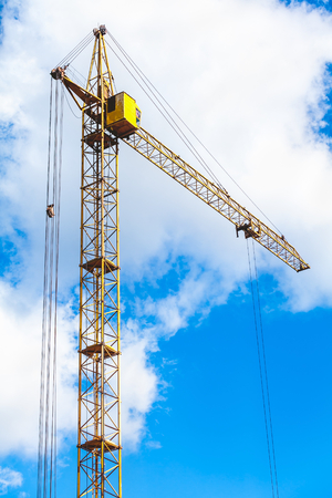 the view from below: Yellow hoisting tower crane on a background of cloudy sky view from below Stock Photo