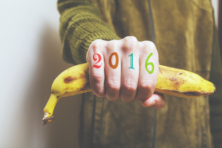 0 1 years: Man in  green jacket holding a banana in his fist, symbol of a monkey year. Figures 2016 painted on fingers. Stock Photo