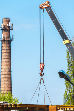 lowers: boom of the crane lowers the load. Behind the high brick chimney boiler