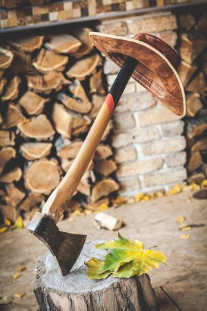 weighs: brown leather hat weighs a long-handled ax, which juts out into the stump