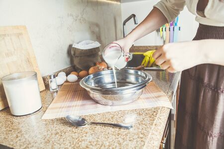 kitchen countertops: Young woman in ethnic clothes pours yogurt in a bowl