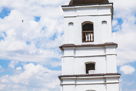 tiers: upper tiers of white stone bell tower on  background of cloudy sky