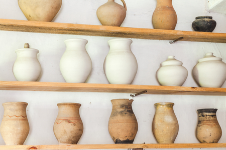 three shelves: Three wooden shelves with old clay jug on white wall Stock Photo