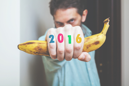 Man holds banana in his hand in front of him. Monkey symbol. On fingers painted figures 2016