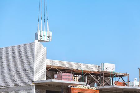 heavy load hanging on the hook of a crane under construction and the construction of a brick chimney boiler