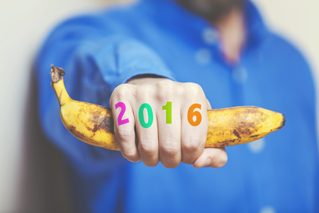0 1 years: Man hand in a blue shirt in his hand squeezes a ripe banana. Symbol of monkey year. Figures 2016 painted on fingers. Stock Photo