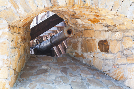 embrasure: Old cast-iron cannon in embrasure medieval stone fortress Stock Photo