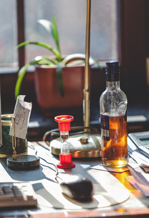 started strong alcohol bottle and hourglass stand on the desktop in the office in sunlight. Behind the pot with a plant Standard-Bild