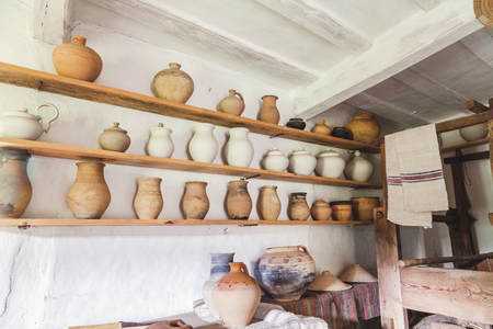 three shelves: Three rows of clay pots on wooden shelves on wall Stock Photo