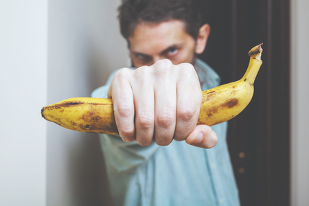 bowed head: Man holds banana in his hand in front of him. Monkey symbol.