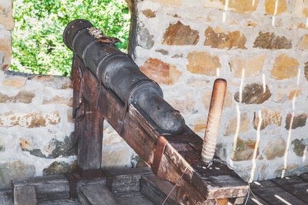 cannon gun: Old cast-iron cannon on  stationary wooden gun carriage from loopholes of fortress wall
