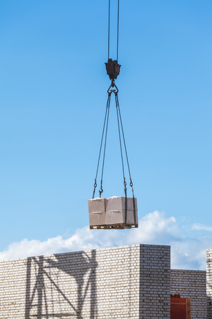 heavy load hanging on the hook of a crane on the construction of brick under construction