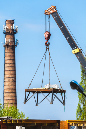 slings: boom of the crane lowers the load. Behind the high brick chimney boiler