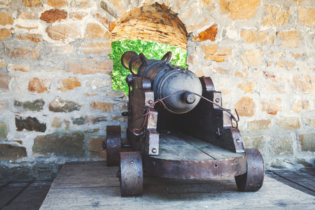 loopholes: Old cast-iron cannon on a wooden carriage at the loopholes of the fortress wall. Back view Stock Photo
