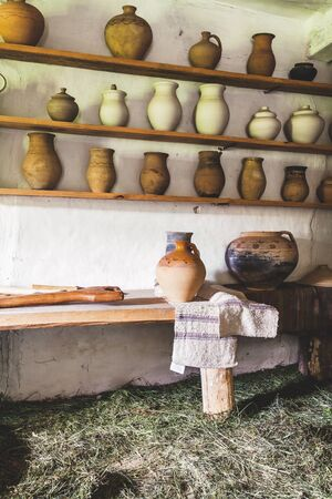 sweetening: Wooden shelves with jugs in house sweetening dry grass
