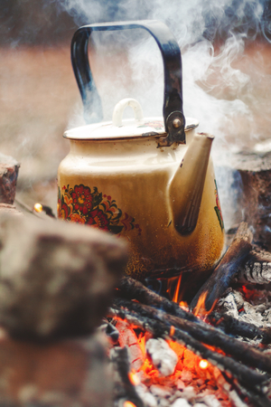 sooty: Metal sooty kettle stands on an open flame fire. Behind the rising white smoke