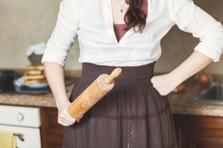 table skirt: The woman in the kitchen holding in one hand a wooden rolling pin and the other rests on the side