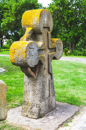 museum visit: Ancient stone cross inscribed mossy side view