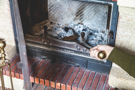 house exchange: Cleaning the fireplace. Hand of man holding a brass shovel with ash Stock Photo