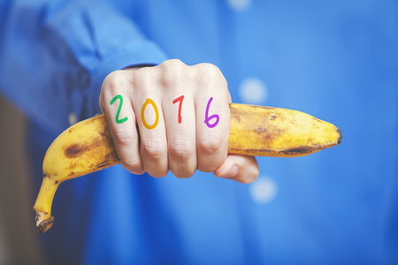 Man hand in a blue shirt in his hand squeezes a ripe banana. Symbol of monkey year. Figures 2016 painted on fingers. Stock Photo